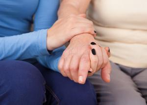 Female Caregiver Consoling Senior Woman